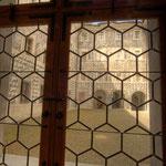 Blick durch alte Putzenscheiben auf den reichlich mit Sgrafitti ausgestalteten Schloßhof