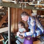 Erwin Permesser zeigt einer jungen Museumsbesucherin das Stricken an einer historischen Strickmaschine