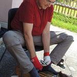 Reinhard Puchinger zeigt einen anstrengenden Arbeitsschritt im Trommelbau-das Beziehen einer Djembe