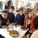 Junge MuseumsbesucherInnen schauen der Steinmalerei von Kathi Herzog zu...