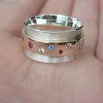Der mittlere Ring ist aus Altgold der Kundin und auf eine breite Silberschiene gesetzt. Die Steine sind bunte Zirkonias