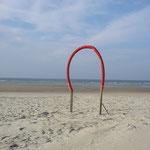 Strandspazierer haben Zeit auf Norderney - zum Beispiel für kreative Kunst am Strand
