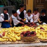 Indigene Kinder beim Zerkleinern von Mais.