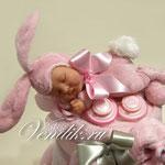 Милый малыш пупсик в пушистом костюмчике розового Зайчонка.