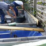 Im Vordergrund die blaue Badewanne für die Überwinterungsgrube, die Männer gleichen letzte Unebenheiten mit Mörtel aus