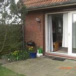 Ansicht Terrasse mit Grill und Gartenstück.