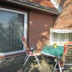 Ansicht Terrasse mit Gartenmöbeln und Strandkorb auf Rollen.