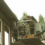 die Werkfeuerwehr der Lebenshilfe Rinteln montiert die Nisthilfen und die liebevoll bemalten Kotbretter, während der NDR filmt