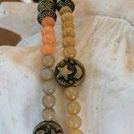 Lange Mala Perlenhalskette Perlen Halskette Clairy mit hellgelben, orangen & khaki Katzenaugen Glasperlen, Bronzerondellen, Bronze Metallperlen Mond und Stern, weisse Quastenanhänger aus Lederimitat