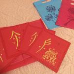 Caractères nüshu à la feuille d'or sur carré de papier Canson rouge