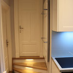 kleine Treppe mit beleuchteten Stufen führt von der Küche aus in den nächsten Raum