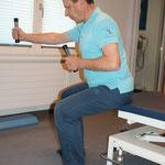 erhöter Sitz, Rücken gerade, mit leichter Vorneigung des Oberkörpers, mit kleinem Gewicht Arme abwechseln nach vorne bewegen