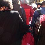 大勢の観光客で埋め尽くされた道路を、ショッピングカートを引いて歩く地元の女性