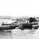"""1894 Vista general de los Muelles de Maliaño durante la explosión controlada de los restos del vapor """"Cabo Machichaco"""". A la derecha, extremo sur de Alfonso XIII; en primer plano, """"La Dársena"""", con la primera Estación de la Costa en el espigón"""