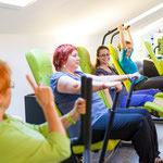 Eine Gruppe macht Muskelaufbautraining an Rücken College Trainingsgeräten