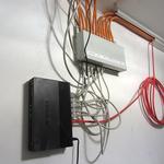 Ein Heimnetzwerk muss nicht zwingend aus Komponenten wie einem Serverschrank oder ähnlichem bestehen. In meinem Fall tut es ein einfacher Switch (schwarzer Kasten) sowie ein Patchpanel (grauer Kasten), welches das Gegenstück zu den Netzwerkdosen bildet.