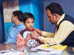 Arzt des S.B. Devi Charity Home untersucht Kinder