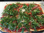 Pizza mit Rucola und Serrano-Schinken