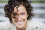 Femme souriante qui peut se développer en harmonie et mieux gérer stress et émotions, une fois que ses réflexes archaïques ont bien été intégrés