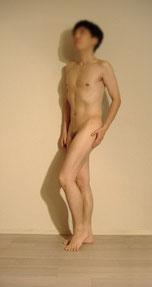 男性ヌードモデルはるきの全裸でポーズをしているイメージ画像。立っている姿勢で片足を爪先立ちにするポーズです。