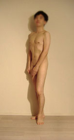 男性ヌードモデルはるきの全裸の姿でポーズをしているイメージ画像。立っている姿勢で片手を男性器(ちんこ)全体をさわるように手で覆うっています。