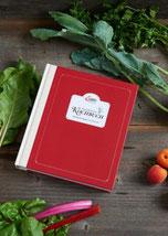Das Kochbuch liegt auf einem Holztisch neben Lebensmitteln.