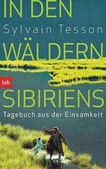 Der Autor spielt mit seinem Hund vor einem schönen See.