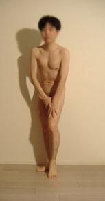 男性ヌードモデルはるきの全裸の姿でポーズをしているイメージ画像。前傾姿勢で片足を少し爪先立ちしその足に両手をついています。