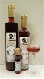 Zirbenschnaps in kräfitger Farbe wird in drei unterschiedlich großen Flaschen und einem Glas präsentiert.
