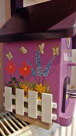 Nestkastje paars, houten beschilderd nestkastje, paars, bloemen, wit hekje, leuk vogelhuisje