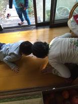 縁側でスタッフと子どもが頭を突き合わせて夢中で遊んでいます。
