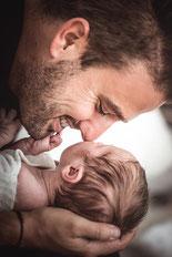 Ein Vater hält sein Neugeborenes und stupst es mit der Nase an die Wange festgehalten von der Familien Fotografin Monkeyjolie in der Ostschweiz