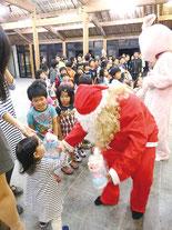サンタクロースからプレゼントをもらってみんな大喜び=22日夜、竹富島まちなみ館