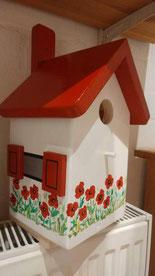 Nestkastje met rood dak en rode klaprozen