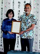 加賀谷陽平部長(右)から藤原さんに任命証が手渡された=30日、市役所市長室