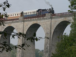 le train avec sa locomotive à vapeur sur un viaduc