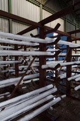 """Detailansichts der 800 kg schweren, 2 meter langen  54 Eisstäbe auf einen Eisengerüst in einer Eisenlagerhalle liegenden temporären Installation """"EIS EN""""beim sich langsamen Auflösungund dahin schmelzen"""