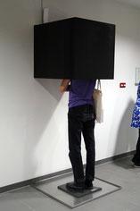 Ein Besucher der Ausstellung Arbeiten der PreisträgerInnendes Diözesankunstpreis in der Kreuzschwestern Galerie für die Betrachtung der Videoinstallation EIS EN im Inneren einer Box, dazu in ein mit Wasser gefülltes Metalbecken steht.