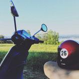 Vespa LX 50 mit roten Helm am Bodensee.
