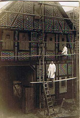 Foto von 1930, zwei Maler auf einem Gerüst vor einem Fachwerkhaus