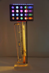 Assemblage light art sculpture consisting of a scientific instrument made of plexiglas, paper and wood with holes illuminated with LEDs from behind, refracted light created by lined plexiglas, and circles of old French checks which cover the holes.