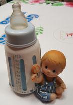 Figura para tarta bautizo. Biberón azul con niño sentado con hucha.  1450. 20 cm aprox