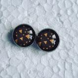 12 mm Edelstahl Ohrstecker gelbe Dreiecke asynchron auf dunkelgrauem Hintergrund