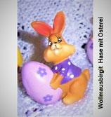 Osterfigur - Hase  mit fliederfarbenem Ei in kleiner Geschenktüte