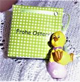 Osterfigur - Entenküken mit fliederfarbenem Ei in kleiner Geschenktüte