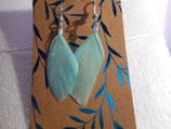 Oorbellen met licht blauwe veertjes.
