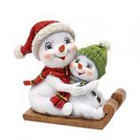 Schneekinder auf Schlitten