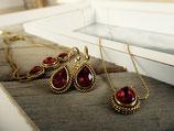 Goldene Ohrringe, Halskette und Armband mit dunkelroten Steinen
