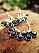 Silberne Ohrringe und Halskette mit schwarzen Steinen
