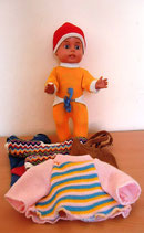 Kleine Puppe mit Anziehsachen